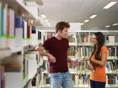A Boy Flirting with a Girl in a Library